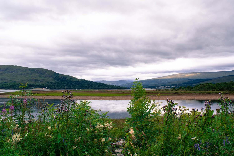 Fort William, Aussicht auf einen See, davor bunte Blumen
