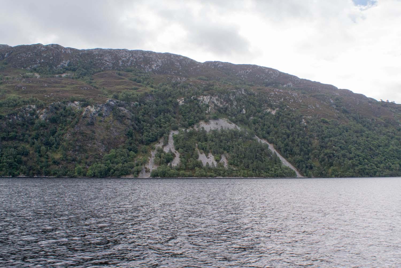 Loch Ness, man sieht an den bewaldeten Klippen eine kahle Stelle, als ob ein riesiges Wesen versucht hat dort aus dem Wasser zu kommen.